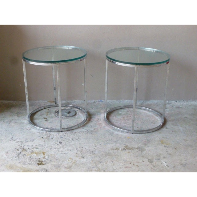 This is a pair of Milo Baughman or Dia chrome circular tables, circa 1970. The pieces feature glass tops and are unsigned...