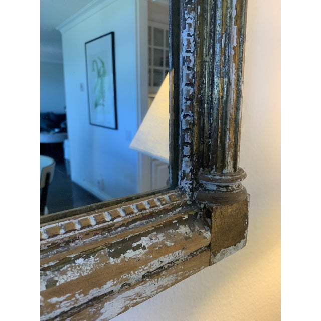 Frame consists of fluted columns topped with Corinthian columns flanking the center mirror. The top portion features...
