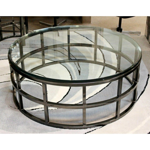 For your consideration is a marvelous, round coffee table, with a glass top on a gunmetal base, by Brueton circa the...