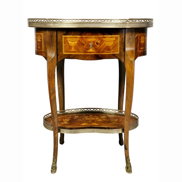 Oval top with inlays and brass gallery over a drawer with all around inlays, raised on shaped cabriole legs and a lower...
