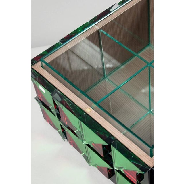 Unique glass box, composed of numerous mirrored segments of green and red colored glass. The gray-tinted oak interior...