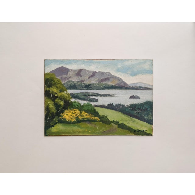 Picturesque, vintage oil landscape painting by artist, C. Madahm. The serene painting features a lake with purple...