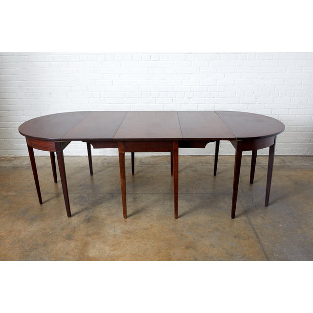19th century English Hepplewhite style mahogany three part banquet or dining table. Set consists of one drop leaf table...
