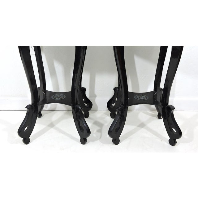 A rare pair of stunning Asian black lacquer side tables or pedestals, exquisitely inlayed with mother of pearl throughout....