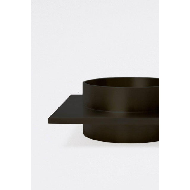 This contemporary dish made of blackened brass is part of the Orphan Work brand and can be used as an table top object....