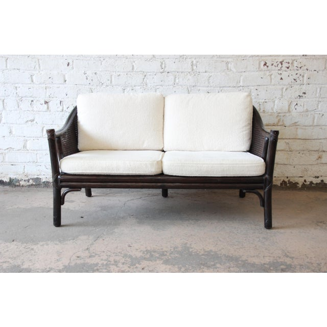 A gorgeous vintage rattan and cane settee or loveseat by McGuire. It features expertly crafted hardwood and rattan...