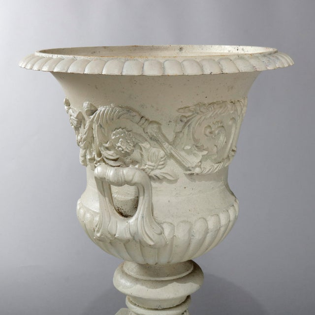 An antique French neoclassical garden urn offers central foliate and scroll relief band and double handles, seated on...