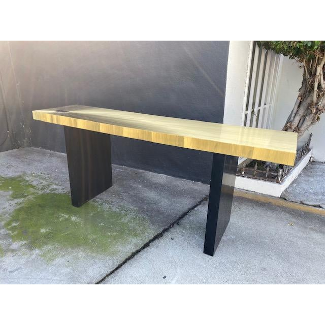 Beautiful Soleil brass console table. Bright gold with black wood legs.