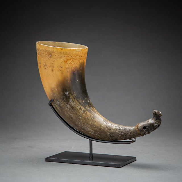 Horn vessel of graduated colour, tapers at one end and sculpted in the shape of a kneeling ram wearing collar; tooled...