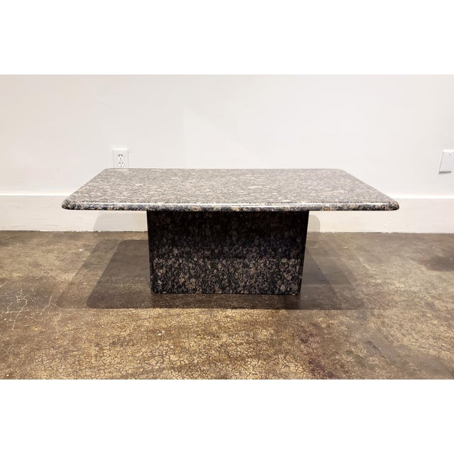 1980's Italian Baltic granite coffee table. Beautiful large specs of tan, grey, brown, black and white. Beveled, rounded-...