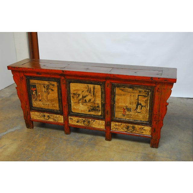 Large Chinese sideboard featuring a hand painted lacquer finish with scenes on the three front doors. This elongated side...