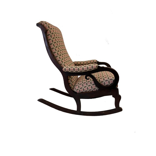 Antique Empire style rocking chair of mahogany or walnut with serpentine back, scroll arms, small carved egg-scallopy...