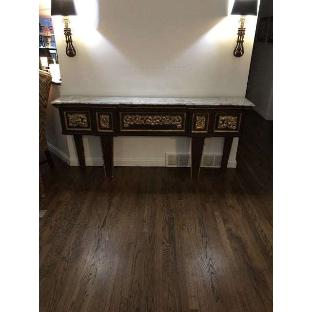 Antique neoclassical tall and narrow console table. Faux marble top shows paint loss. Table is old and shows age related...