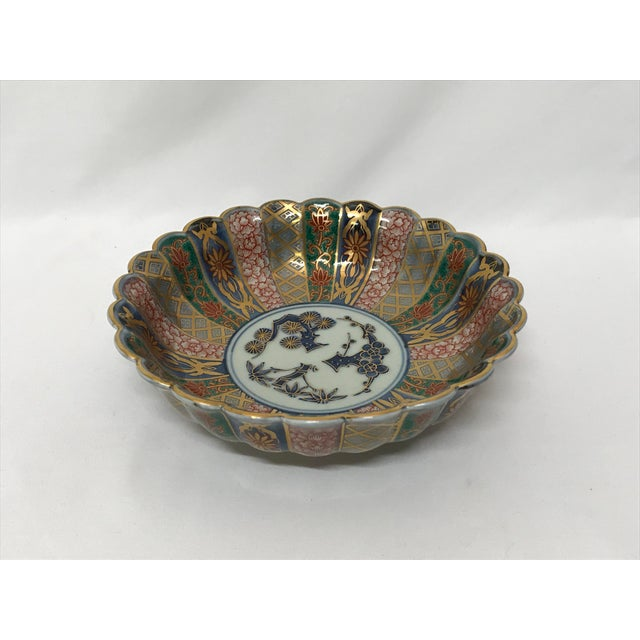 Antique Chinese Imari scalloped edge bowl with gilt decorations and flow blue interior motif. Marked on underside.