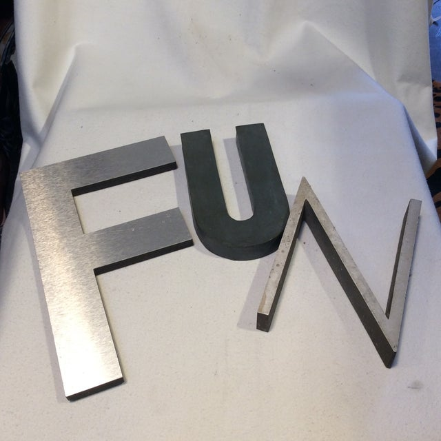 a set of vintage metal letters that spell fun these are roughly 20