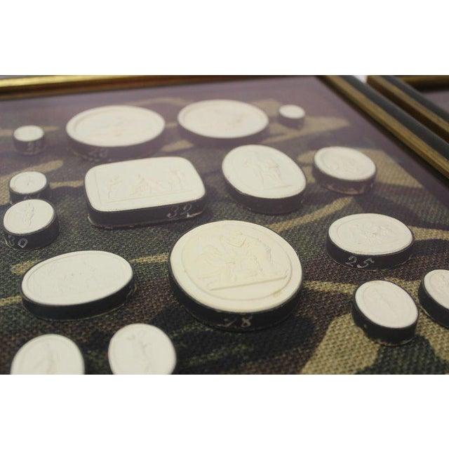 Antique plaster intaglios whimsically framed on camouflage burlap, the intaglios are numbered and correspond to the...