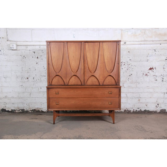 An exceptional and iconic mid-century modern sculpted walnut gentleman's chest by Broyhill Brasilia. The chest has...