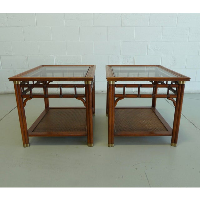 Beautiful vintage faux bamboo and cane chinoiserie style side tables. The tables have intricately carved details, brass...