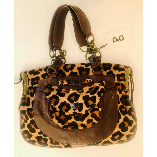 Stylish leopard fur and leather purse by D&G. Soft brown leather detail with real fur inset. Colorful fabric interior....