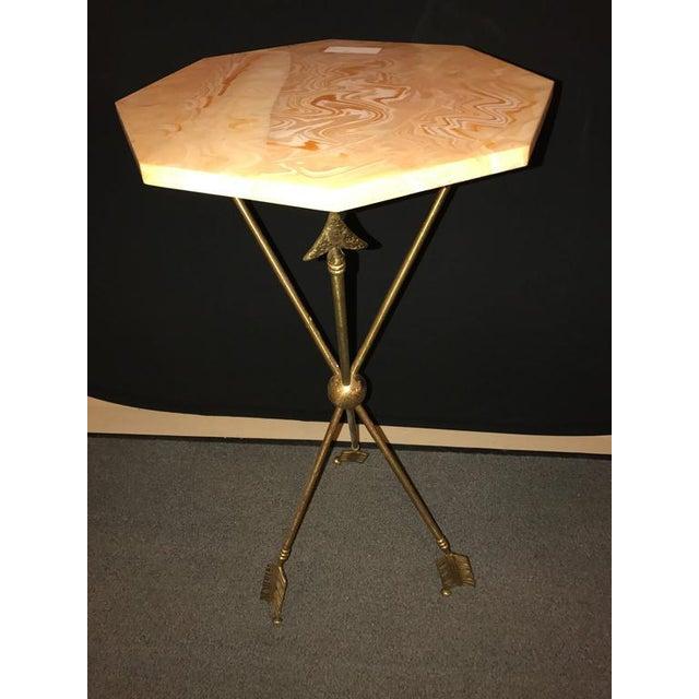 An arrow form bronze table base on tri pod legs.
