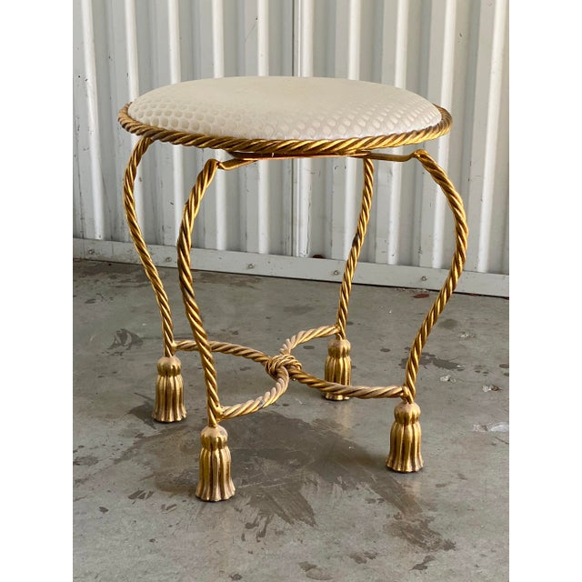 Beautiful twisted brass vanity stool. Four gold tassels create the feet for this piece. Ivory jacquard upholstery....