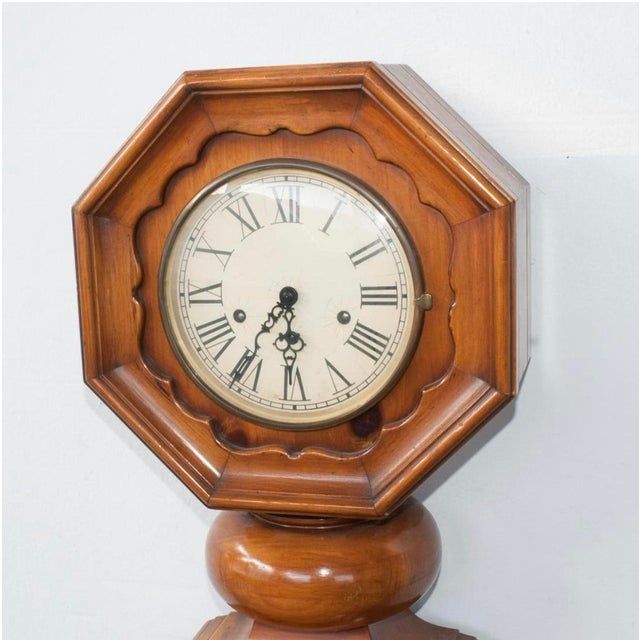 A German, F. Mauthe, granddaughter clock. Composed of an overall wooden foundation with a tapering base, designed with...