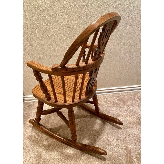 Early 1900s English rocking chair with unique quality spindled legs and cutout back design make this piece a rarity and a...