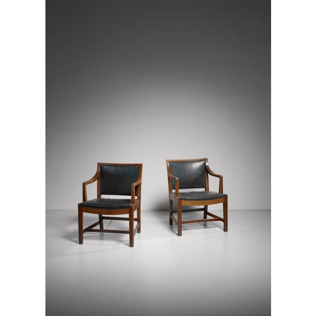 A pair of armchairs made of beech, upholstered with a dark green leather. These chairs were used on the Kong Frederik IX...