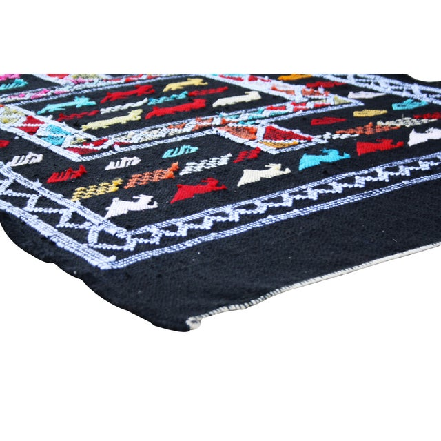 Handwoven Moroccan Berber wool kilim with ornate geometric shapes. Would also make an eye-catching wall hanging!