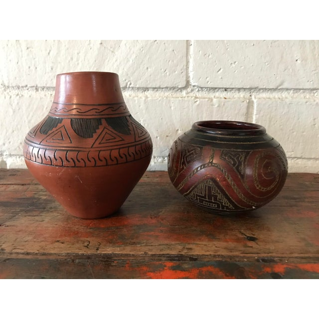 Set of two Navajo Pottery vases in warm shades of brown. Hand carved details on both. Made of clay. Both in great...