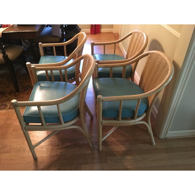 Set of four Mcguire bamboo dining chairs with aqua cushions. Minor damage to one arm.