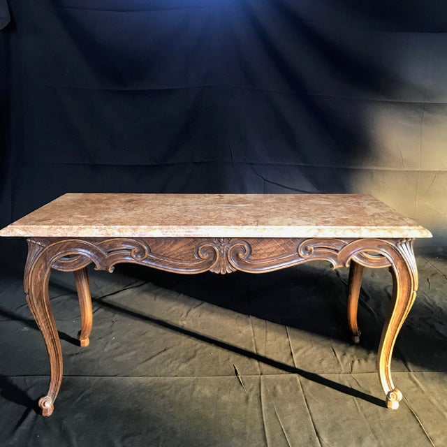 A stunning antique French coffee table having a Louis XV form with an entire walnut frame carved in ribbon design with...