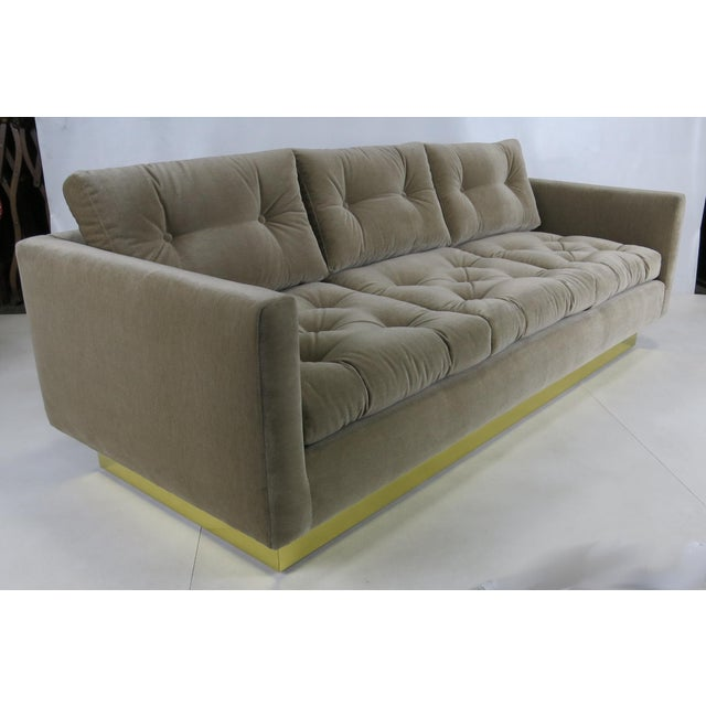 Handsome tufted velvet sofa with Brass clad base by Milo Baughman. The sofa has been freshly reupholstered and the brass...