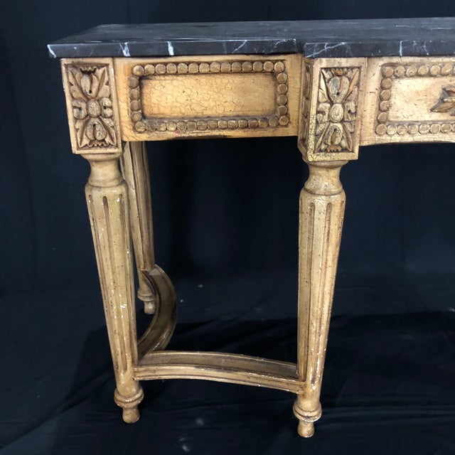 Louis XVI style console table having white and gold veined black marble top on very well carved frieze and legs and a...
