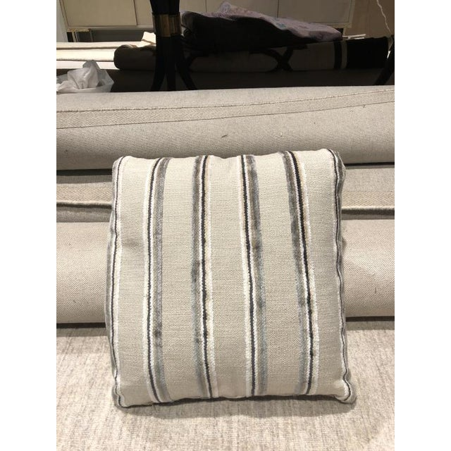 The Style B2 throw pillow is a first quality showroom sample that features a beige patterned fabric with welted corners...