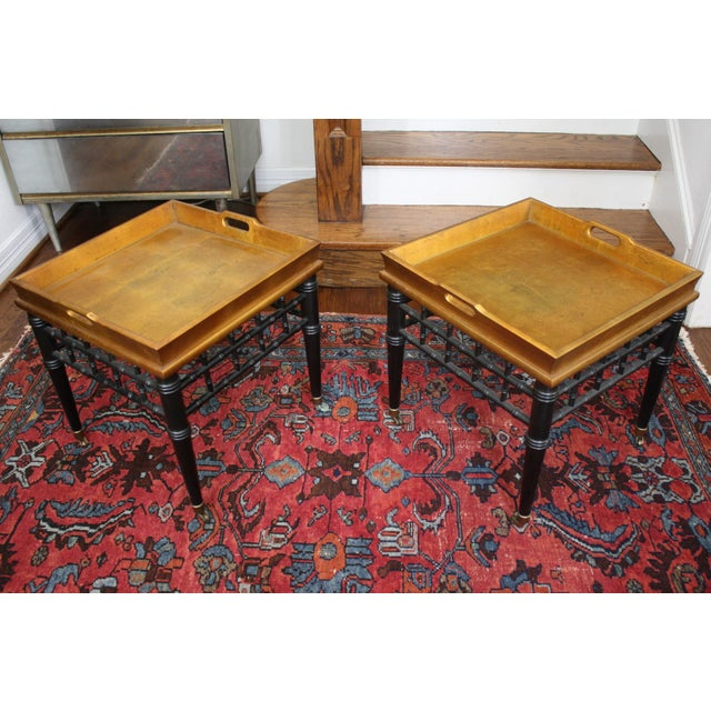 Pair of Mid-Century Asian influenced faux bamboo tray tables with gold leaf tops, black lacquered bases and rollers on the...