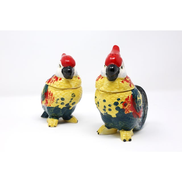 A vintage ceramic salt and pepper / cream and sugar set, in the form of two colorfully hand-painted birds. The heads are...