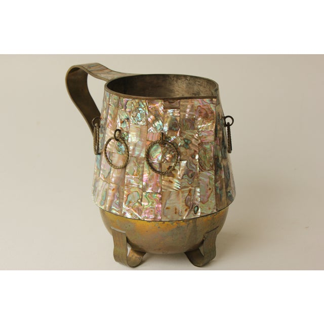 1950s Mexican water pitcher by Salvador Teran, featuring twisted brass rings and abalone shell inlay. Its original patina...