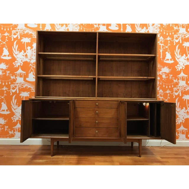 Drexel Declaration Credenza is constructed of Walnut and is a 2 piece unit. The shelves are constructed of wood frames...