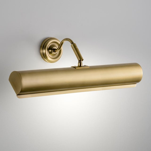 An English brass picture wall light with a detailed backplate and swan neck arm with swivel joints. The tubular canopy has...