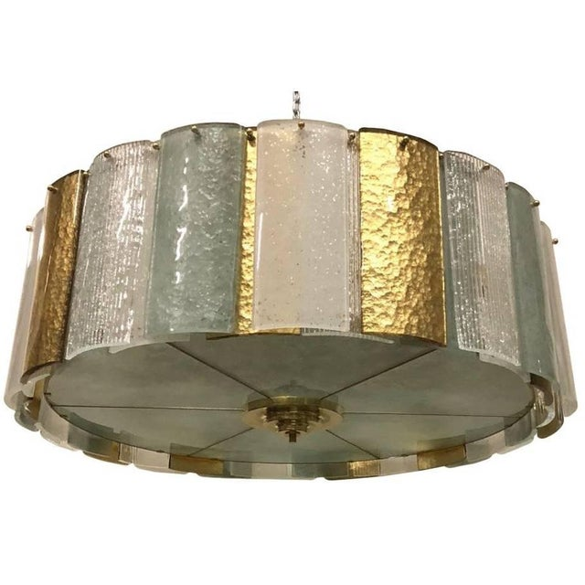 Italian modern chandelier shown in clear ribbed, teal, frosted, and gold Murano glass panels, mounted on polished brass...