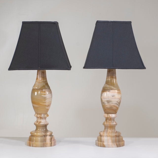 A pair of large scale onyx table lamps, solid and stable. The lamp shades and harps are not included in the sale. Onyx, an...