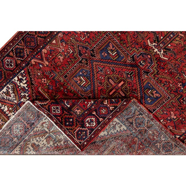 Beautiful Vintage Persian Heriz hand-knotted wool rug with The red field. This rug has accents in blue, brown, and Ivory...