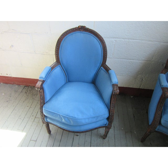 Fabulous pair of antique petite French bergeres with blue upholstery and highly carved walnut frames. Cushions filled with...