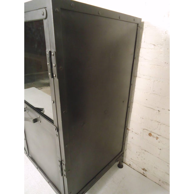 Heavy duty industrial style metal cabinet with glass top doors. Features handsome exposed rivets and metal latches for...