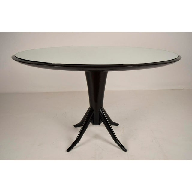 This is a stylish 1960's dining table made of a solid mahogany wood frame and finished in a rich deep black color. There...
