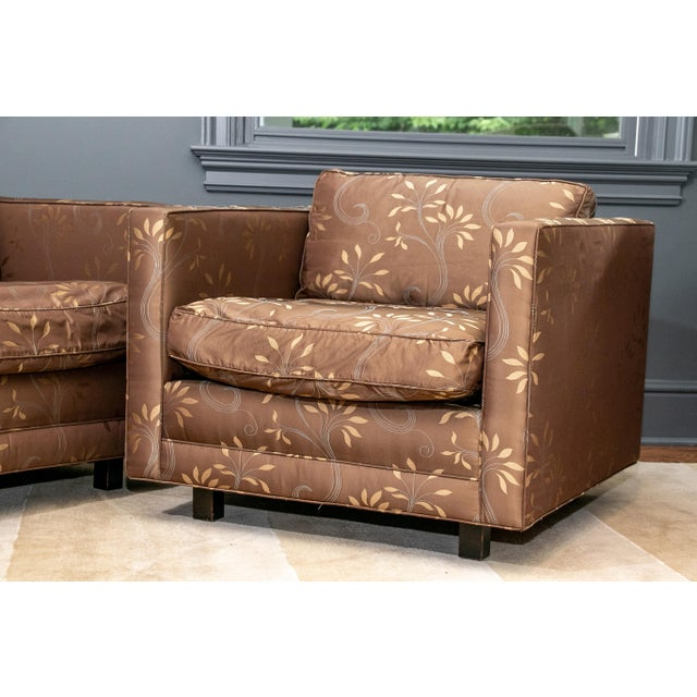 Square frames with seat and back cushions, raised on square black recessed feet. Upholstered in a silky brown and gold...