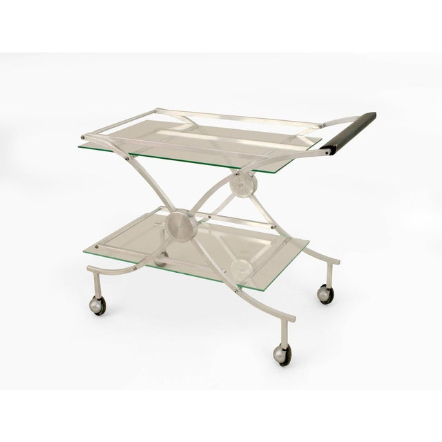 """American Art Moderne 1930s-1940s aluminum bar cart with """"X"""" design sides supporting a glass top and shelf with an ebonized..."""