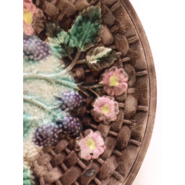 A very pretty antique Majolica plate with a basketweave design. The center portion of the plate depicts flowers in pink...
