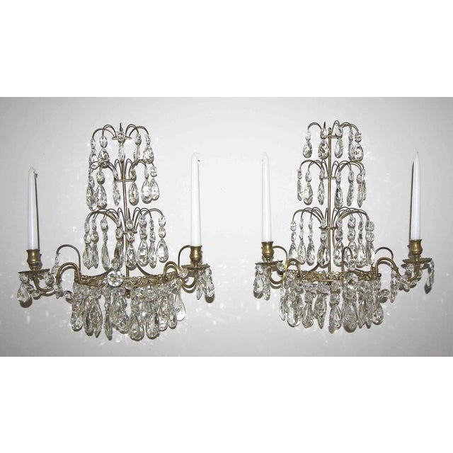 Pair of exquisite crystal and brass Swedish two-arm candle wall sconces. Nice detailing to the metal work with graceful...